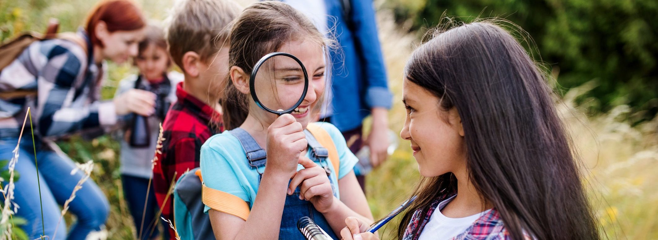 Girls outdoors exploring; one holding a magnifying glass and the other looking at the girl with a notepad