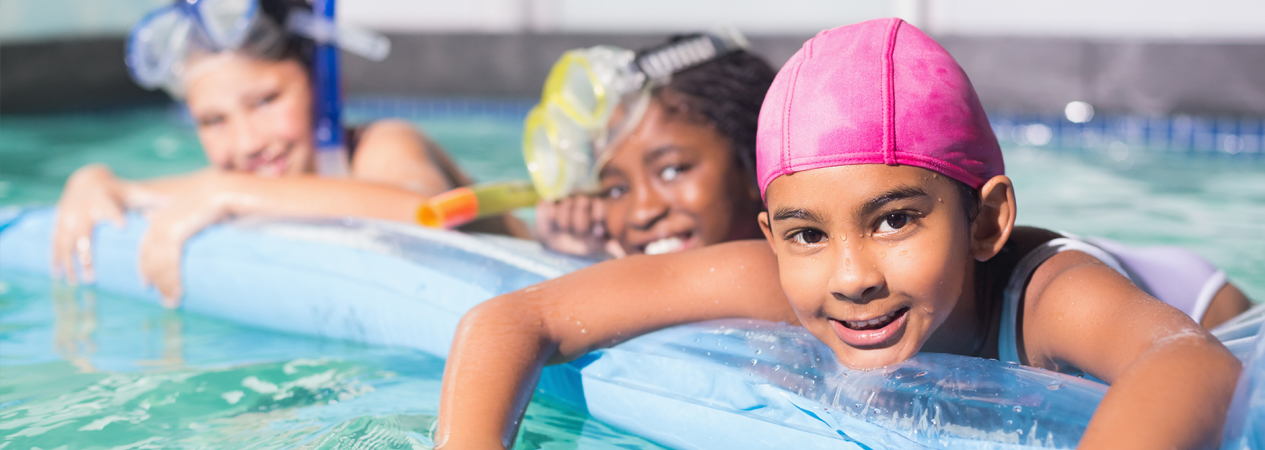 a few children floating on a pool noodle smiling in the pool