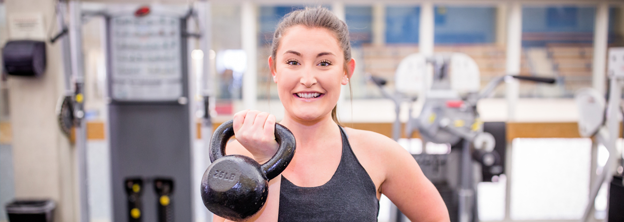 Caisse in weight room holding a kettle bell smiling
